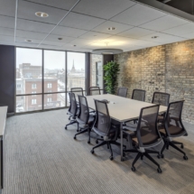 meeting-room-light-grey-striped-pattern-rug-area_brown-fabric-upholstered-meeting-chair_cream-stained-wooden-meeting-table_natural-silver-aluminium-frame-clear-glass-ventilation-window